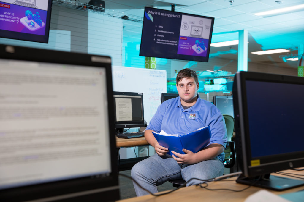 Eli Evans faces the camera, with computer monitors in the background