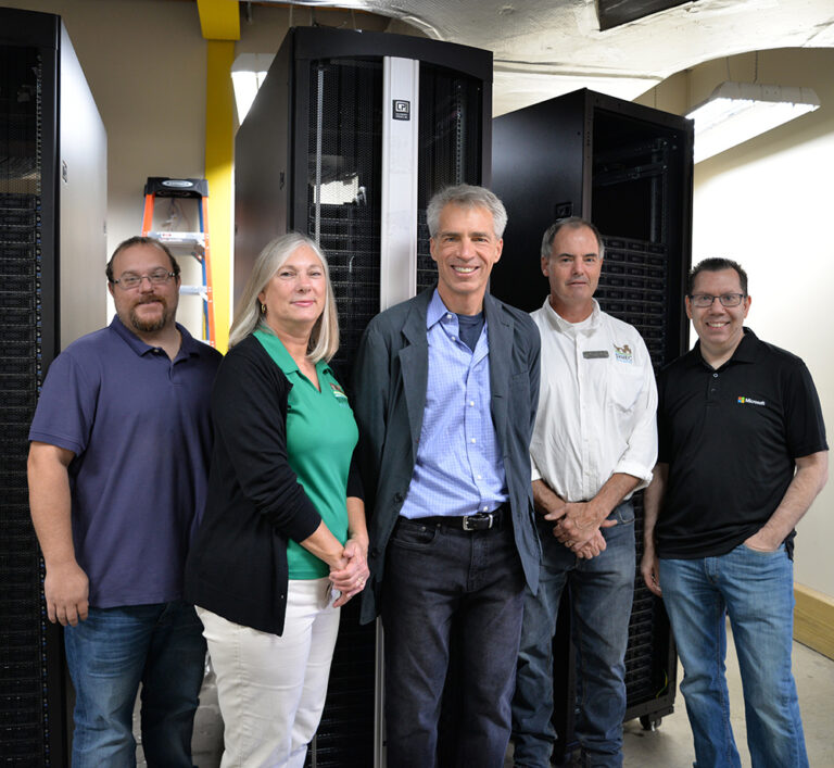 Representatives from Microsoft stand with SVHEC staff in front of a newly donated, decommissioned Microsoft server.